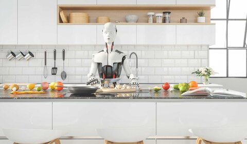 Robot stands in the kitchen preparing food
